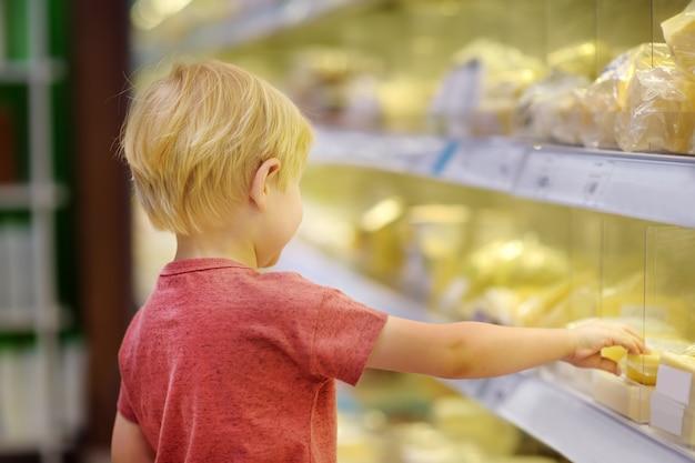 Rapaz pequeno bonito em uma despensa ou em um supermercado que escolhem o queijo e a manteiga, leiteria fresca. estilo de vida saudável para a família com crianças