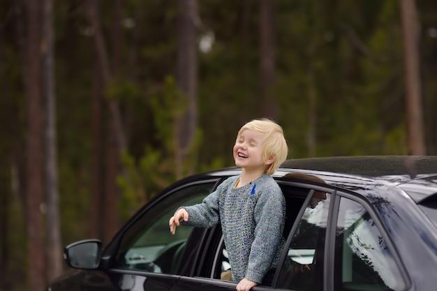 Rapaz pequeno bonito pronto para um roadtrip ou curso. viagens de carro da família com as crianças.
