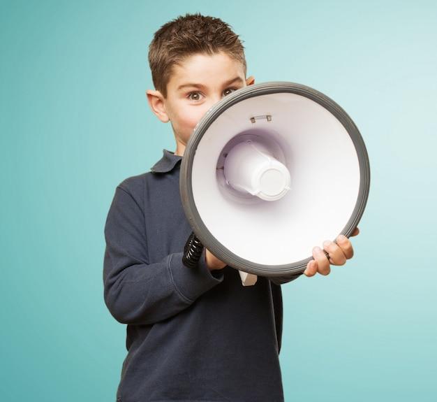 Rapaz pequeno bonito que usa um megafone