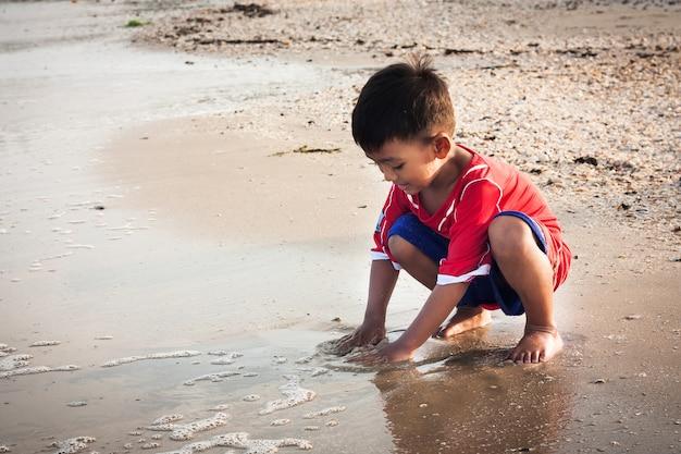 Rapaz pequeno brincar na praia
