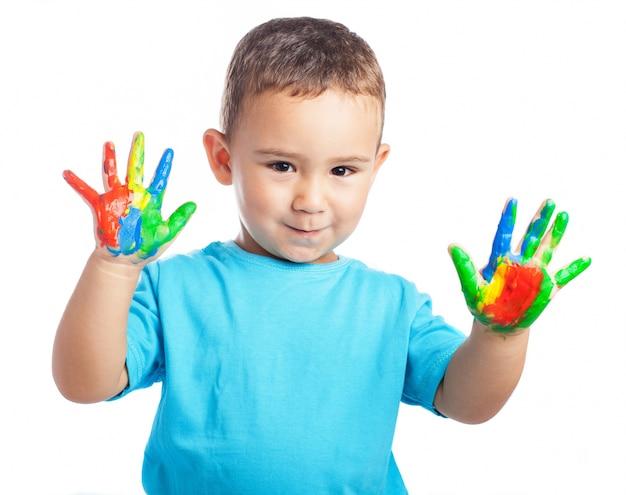 Rapaz pequeno com mãos com tinta