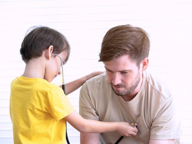 Rapaz pequeno com o stethscope que joga como o doutor que examina o paciente do pai em casa.