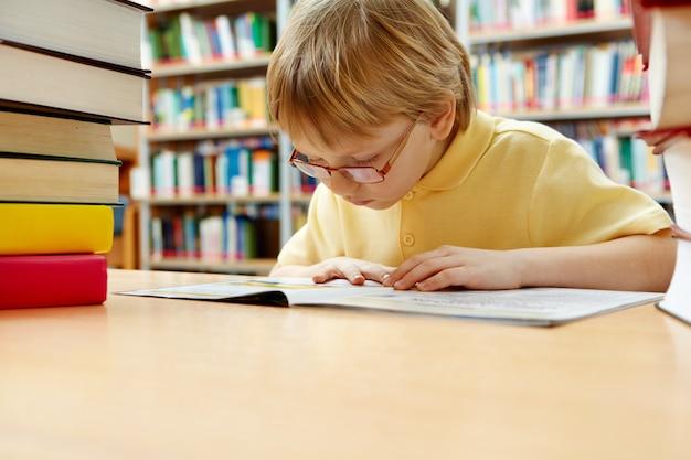 Rapaz pequeno com óculos de leitura na biblioteca