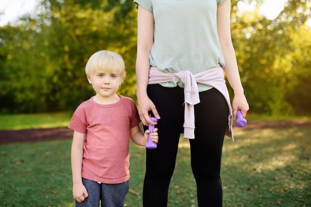 Rapaz pequeno com sua mãe no treinamento com pesos.