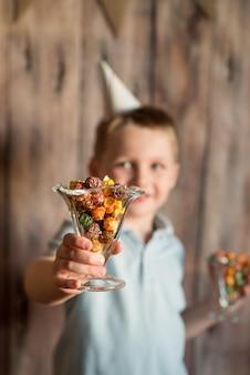 Rapaz pequeno de riso alegre feliz em uma festa. detém uma pipoca colorida em um copo.