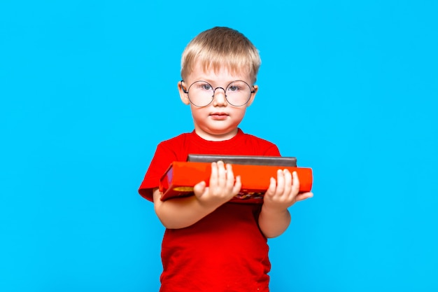 Rapaz pequeno de sorriso nos vidros redondos que guardam uma pilha de livros. educação. pronto para a escola