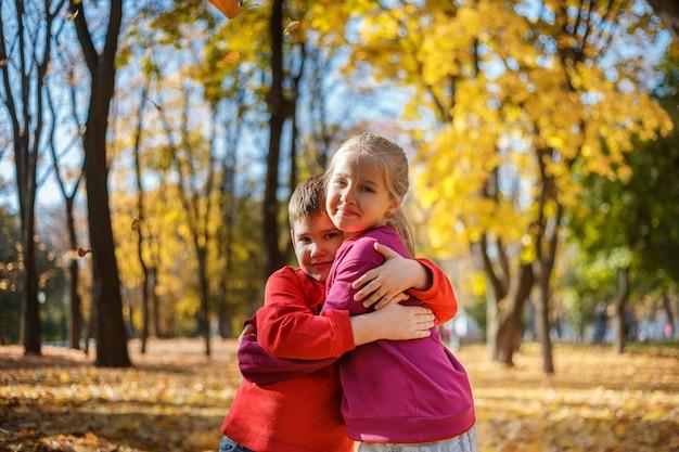 Rapaz pequeno e menina em um parque no outono. garoto abraçando uma garota