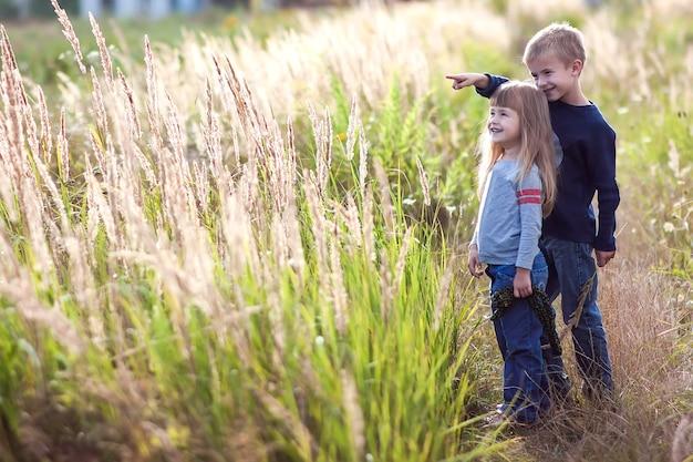 Rapaz pequeno e menina que estão de mãos dadas que olham no horizont. visão traseira.