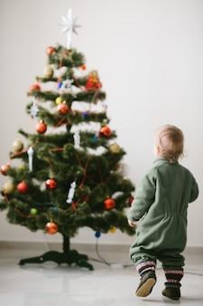 Rapaz pequeno em saltadores verdes anda até a árvore de natal