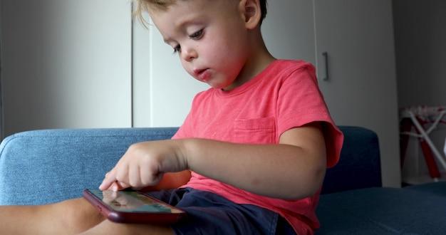Rapaz pequeno encantador que senta-se no sofá azul em casa e que joga o jogo no smartphone