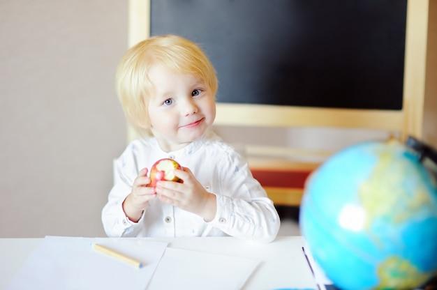 Rapaz pequeno feliz que tira e que come a maçã no local de trabalho.