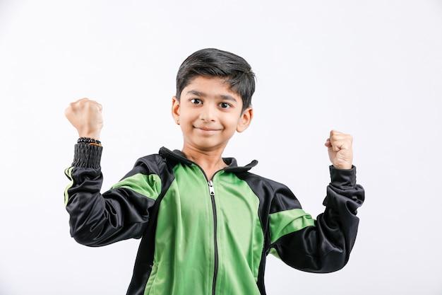 Rapaz pequeno indiano bonito que joga e que dá a expressão múltipla