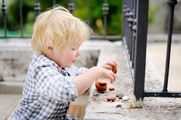 Rapaz pequeno louro bonito que joga com pedras pequenas ao ar livre. criança criança constrói torre