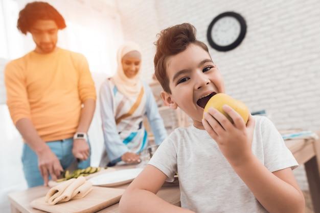 Rapaz pequeno na cozinha que come uma maçã.