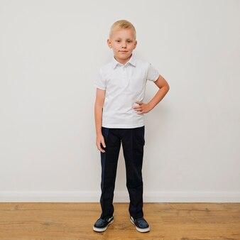Rapaz pequeno na moda à moda em um polo branco e em trouses pretos.