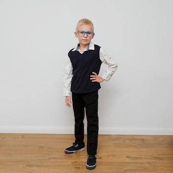 Rapaz pequeno na moda elegante em copos.