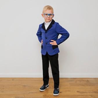 Rapaz pequeno na moda elegante em óculos de terno.