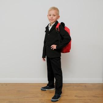 Rapaz pequeno na moda elegante em um terno com uma mochila.