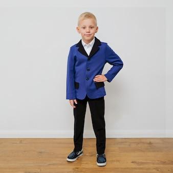 Rapaz pequeno na moda elegante em um terno.
