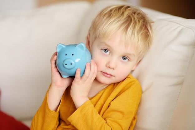 Rapaz pequeno que agita um mealheiro leitão e sonhos do que pode comprar.