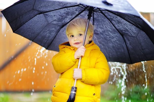 Rapaz pequeno que anda no tempo nebuloso chuvoso do outono. criança com guarda-chuva preta grande na chuva. atividade ao ar livre