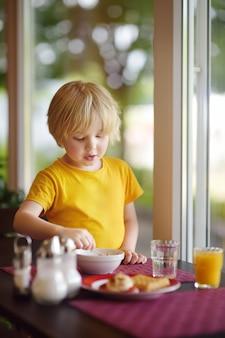 Rapaz pequeno que come o café da manhã saudável no restaurante do hotel. saborosa refeição em casa.