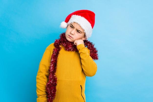 Rapaz pequeno que comemora o dia de natal que veste um chapéu de santa isolado quem sente triste e pensativo, olhando o espaço da cópia.