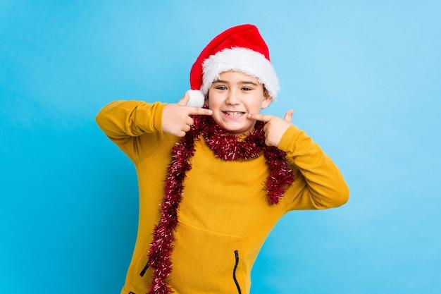 Rapaz pequeno que comemora o dia de natal que veste um chapéu isolado de santa sorri, apontando os dedos na boca.