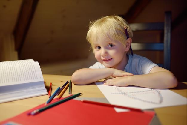 Rapaz pequeno que faz trabalhos de casa, pintando e escrevendo em casa a noite. kid treinamento para escrever e ler.
