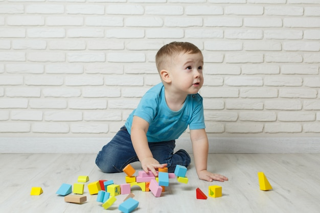 Rapaz pequeno que joga com o construtor no fundo branco. menino jogando blocos brinquedos