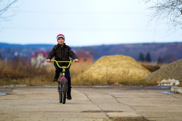 Rapaz pequeno que monta sua bicicleta no parque ao ar livre.