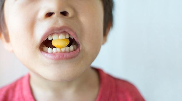 Rapaz pequeno que morde doces amarelos em uma boca com espaço da cópia.