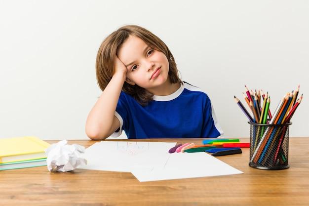 Rapaz pequeno que pinta e que faz trabalhos de casa em sua mesa cansado.