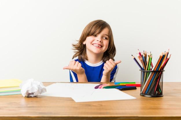 Rapaz pequeno que pinta e que faz trabalhos de casa em sua mesa que levanta ambos os polegares acima, sorrindo e seguros.
