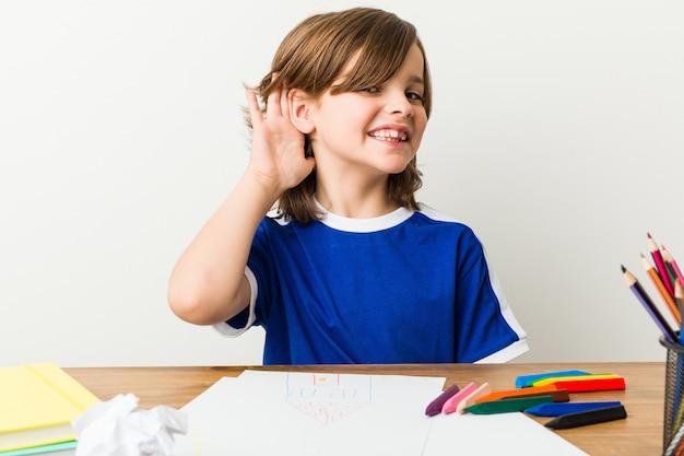 Rapaz pequeno que pinta e que faz trabalhos de casa em sua mesa.