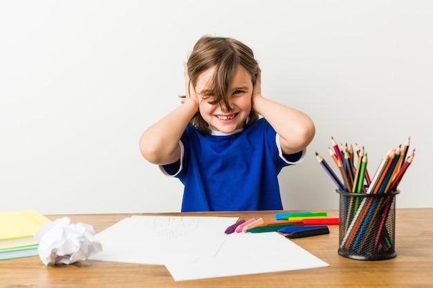 Rapaz pequeno que pinta e que faz trabalhos de casa em suas orelhas da coberta da mesa com mãos.