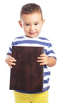 Rapaz pequeno que prende um livro fechado