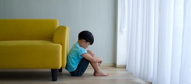 Rapaz pequeno que senta-se ao lado do sofá amarelo em casa. autismo infantil.