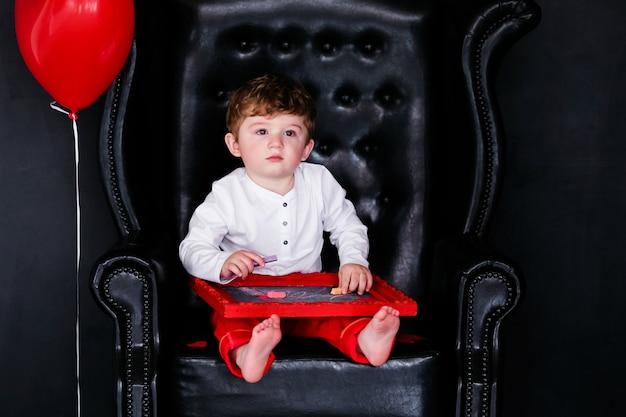 Rapaz pequeno que senta-se na poltrona com imagem quadro vermelha no dia de valentim do st.