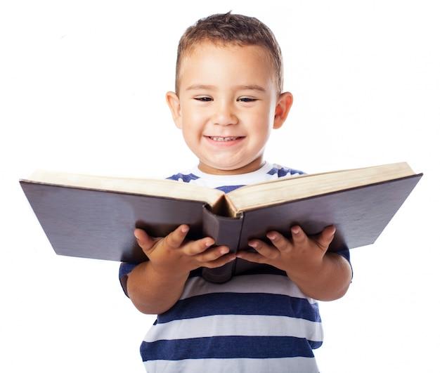 Rapaz pequeno que sorri com um livro aberto
