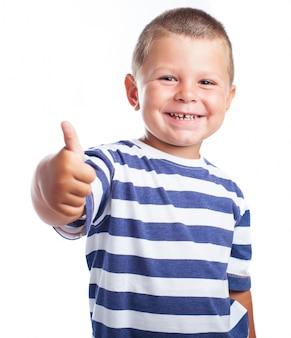 Rapaz pequeno que sorri com um polegar para cima