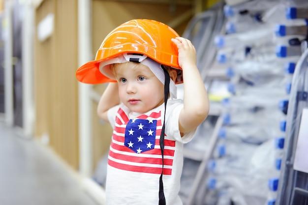 Rapaz pequeno que tem o divertimento em uma loja de ferragens. construtor da criança que escolhe o capacete direito em uma loja de ferragens.