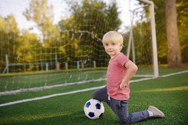 Rapaz pequeno que tem o divertimento jogar um futebol / jogo de futebol no dia de verão.