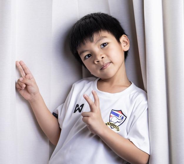Rapaz pequeno que veste a camisa tailandesa da equipe de futebol que suppoting a equipa nacional tailandesa.
