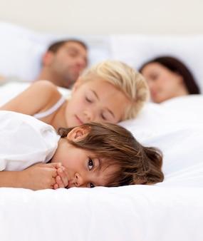 Rapaz pequeno relaxando com seus pais e irmã dormindo