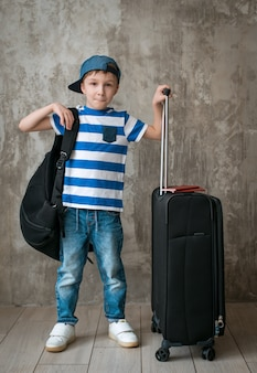Rapaz pequeno sozinho com as malas de viagem contra o muro de cimento no transporte da sala de espera.