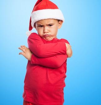 Rapaz pequeno triste com os braços cruzados