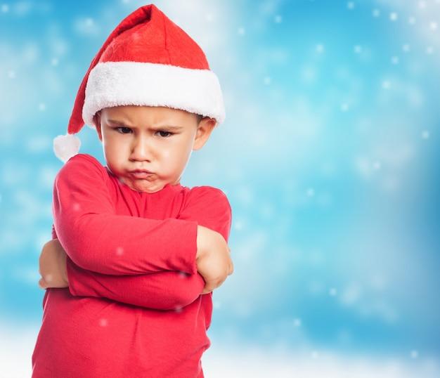 Rapaz pequeno triste que veste o chapéu de santa