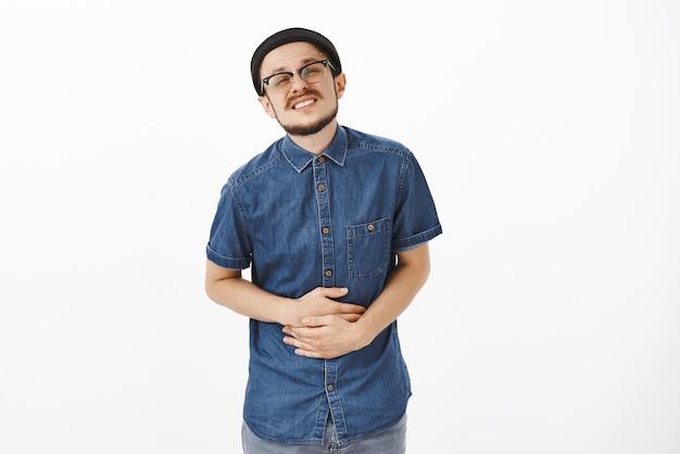Rapaz perturbado comendo comida estragada de mãos dadas na barriga, sofrendo de dor de estômago, cerrando os dentes esperando perto de um banheiro público na fila de pé com sentimentos dolorosos