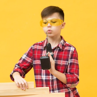 Rapaz posando com máquina de perfuração
